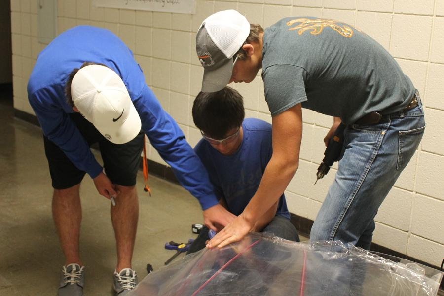 Students work on their electric car the day before a race.