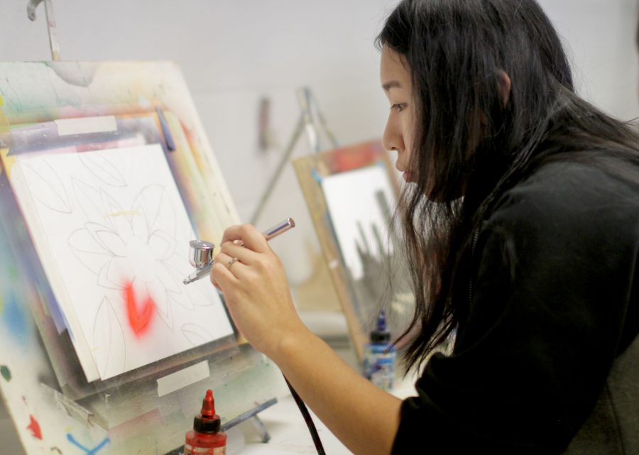 """With a steady hand, senior Korryn Asuncion sprays her drawing of a flower with her air brushing tools in G3 Air Brushing. Asuncion used masking film to keep the color from going places she didn't want it to go. """"This was my first year in Air Brushing and it was difficult at first to control the stream of paint,"""" Asuncion said. """"As the semester progressed, I grasped it and was pleasantly surprised with my work."""""""