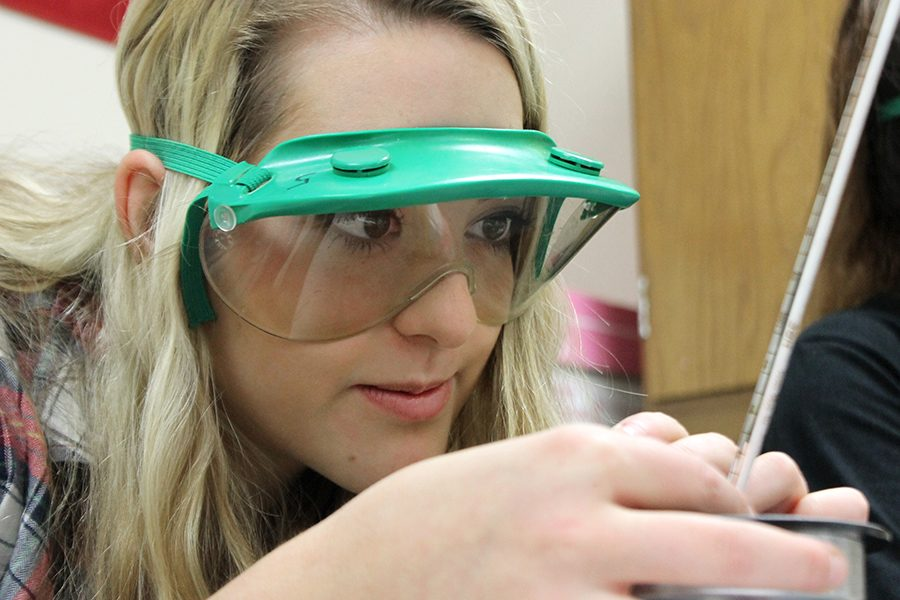 "During Honors Chemistry II, senior Rachel Pendergast reads the thermometer inside the calorimeter. ""This lab was challenging because we had to take very precise readings at various times throughout the experiment,"" Pendergast said. ""I enjoyed this lab because it had a very practical application."""