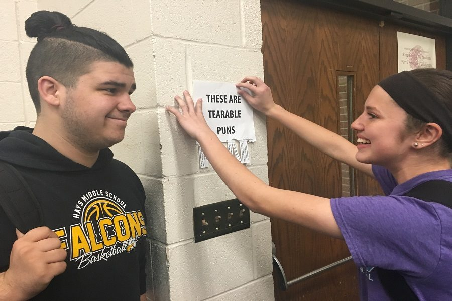 Senior Cooper Flores watches while sophomore Hannah McGuire posts her 'tearable' puns on the wall.