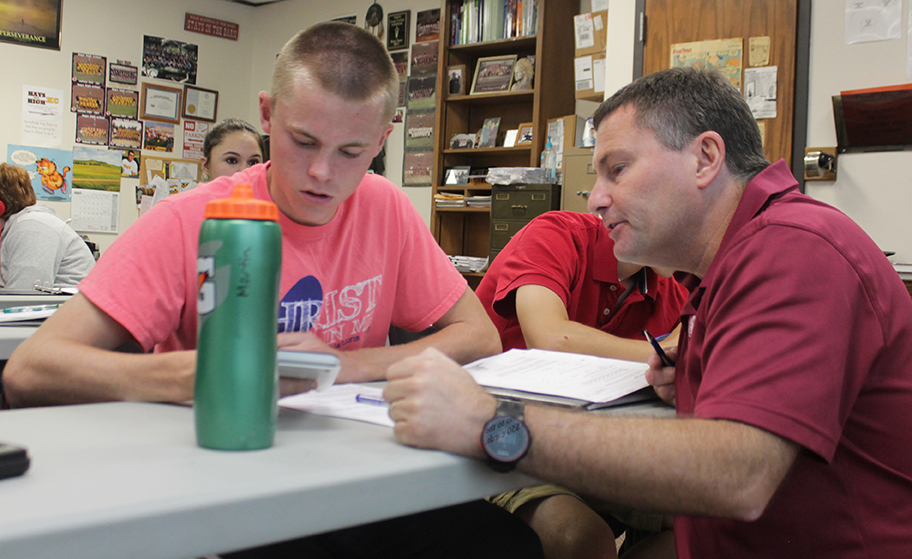 """Going over the class assignment with junior William Staab is Instructor Jerald Harris. Harris is a math teacher who teaches Adv. Algebra I, Adv. Algebra II and Calculus. """"My day consisted of teaching and helping students,"""" Harris said. """"Even when it was my plan I had students in my room needing help."""""""