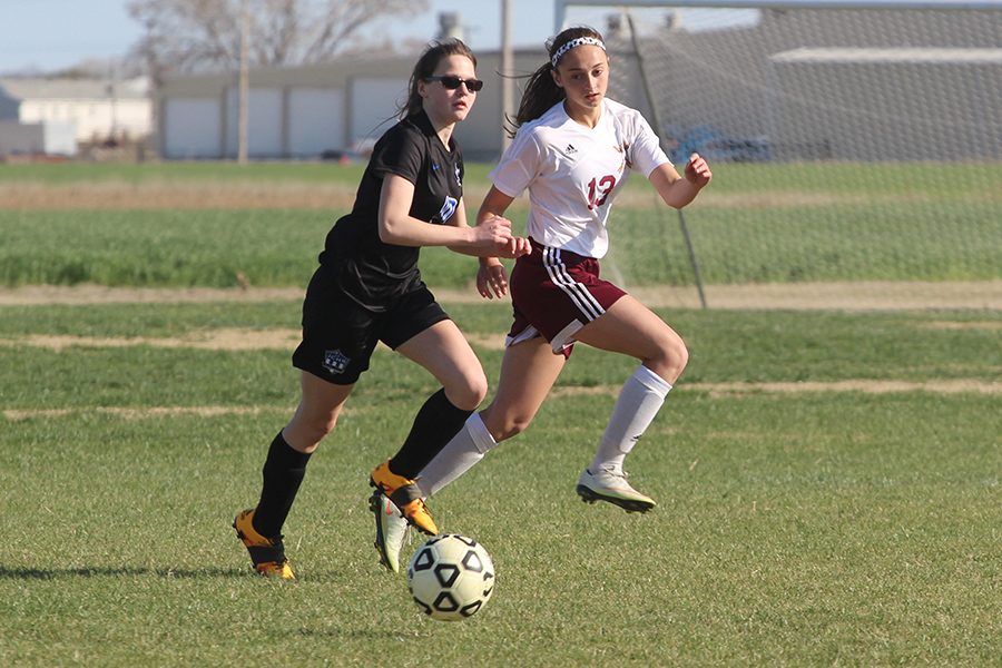 Sophomore Kallie Leiker runs alongside an opposing team member during a recent home game.