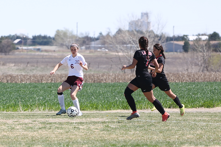 Sophomore  Hannah McGuire takes on two Great Bend defenders in a recent home game.
