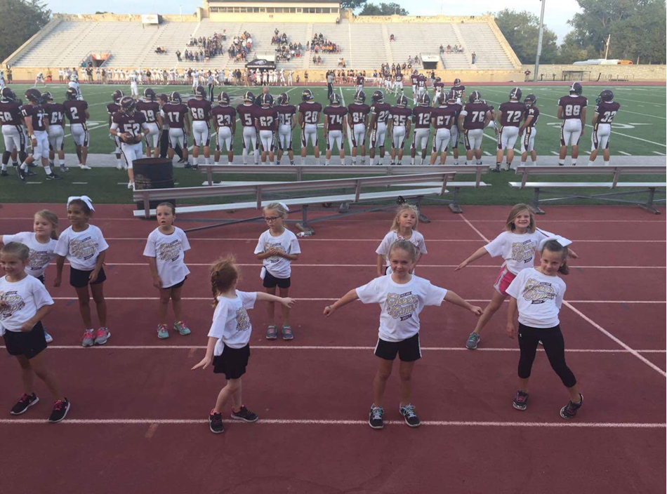 Kids cheering during first quarter of the football game.