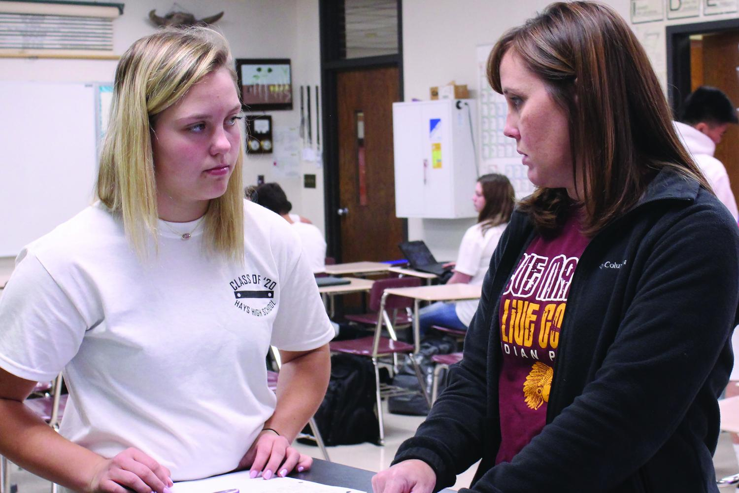 Instructor Beth Schiel helps student Macee Altman with an assignment during Honors Biology.