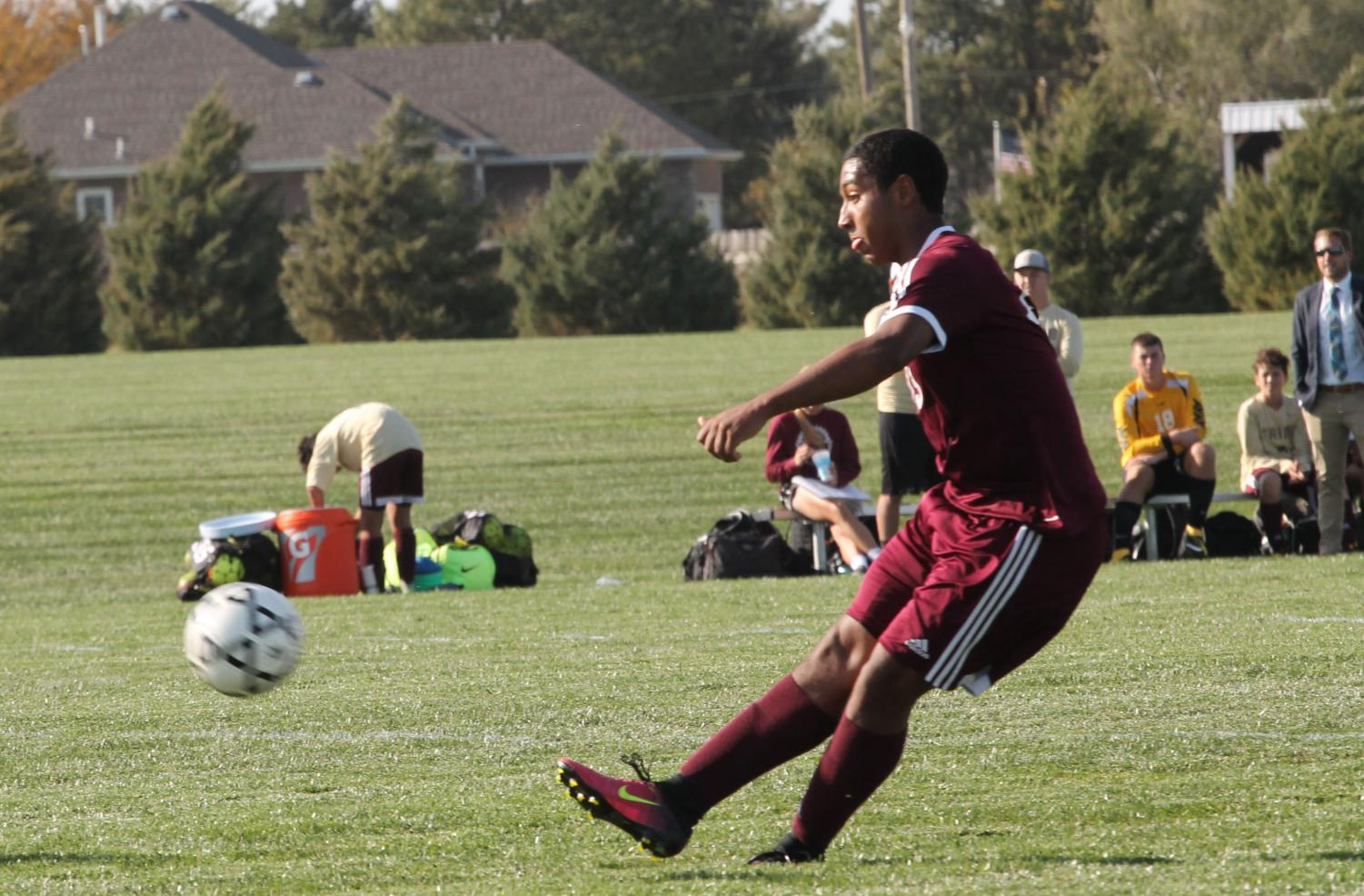 Junior Trey McCrae plays a ball up field to attack the TMP defense in a recent match between the cross town rivals.