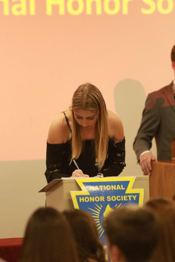 Junior+Myranda+Berner+signs+her+name+in+the+induction+book+during+the+ceremony.+Photo+taken+by+Lindsey++Pfannenstiel.