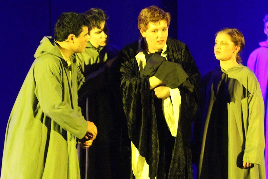 Father Claude Frollo (senior Eric Adams) holds a baby whom he names Quasimodo, or
