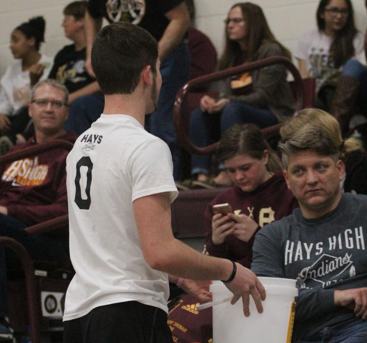 Junior Peyton Thorell collects money from the crowd between the first and second quarters.