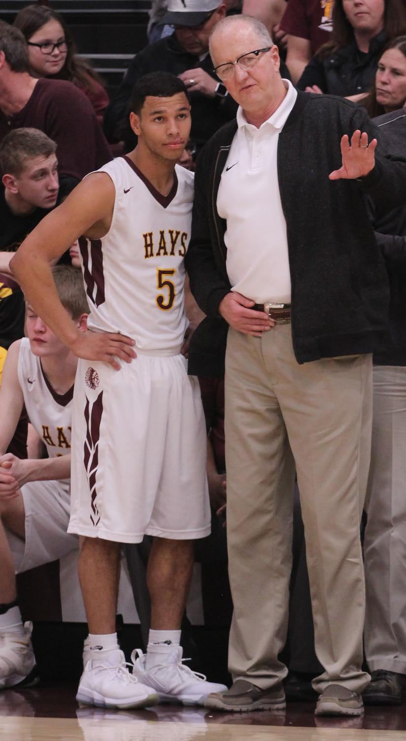 Head coach Rick Keltner instructs senior point guard Ethan Nunnery after coming out of the game.