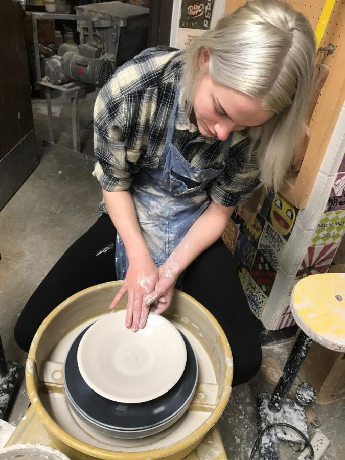 Senior Mikayla Koerner sits at her wheel to make a plate.