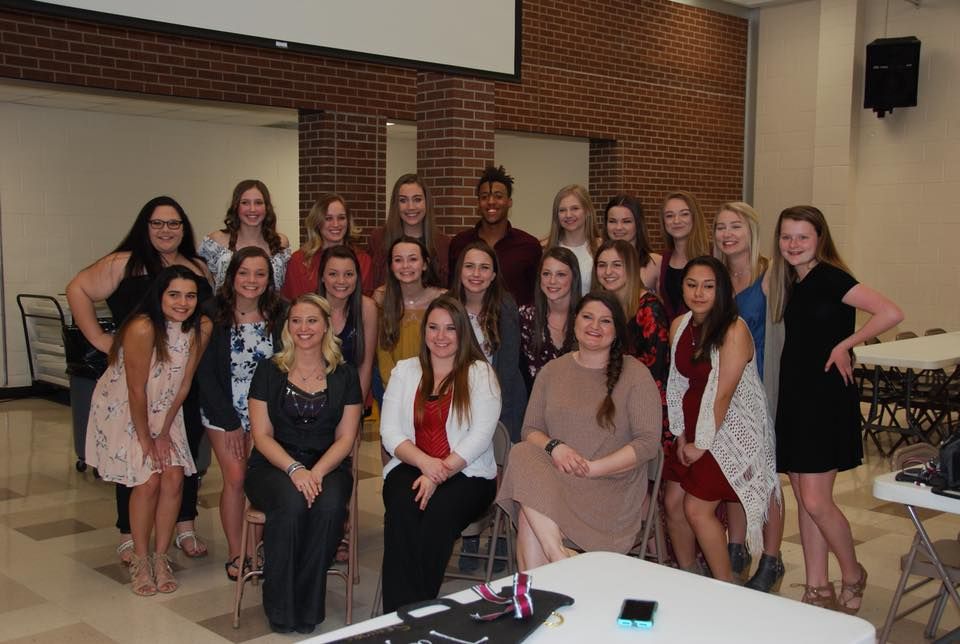 Members of the cheer team pose for a picture with their coaches during the banquet. The banquet was held in the cafeteria on March 13.