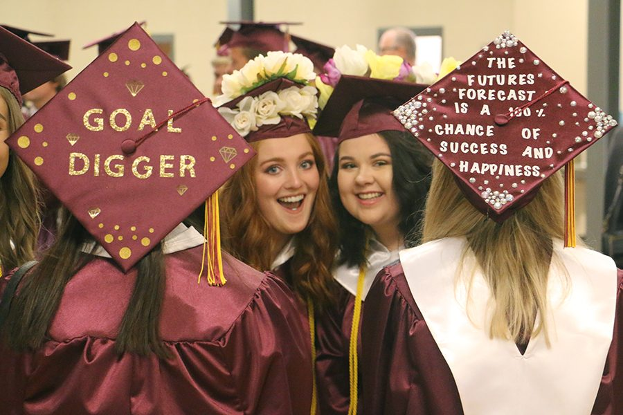 Graduated seniors Hannah Donaldson and Abby Balman wear their decorated caps for graduation.