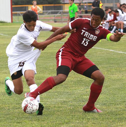 Senior Trey McCrea fights off Garden City Defender to keep control of the ball.