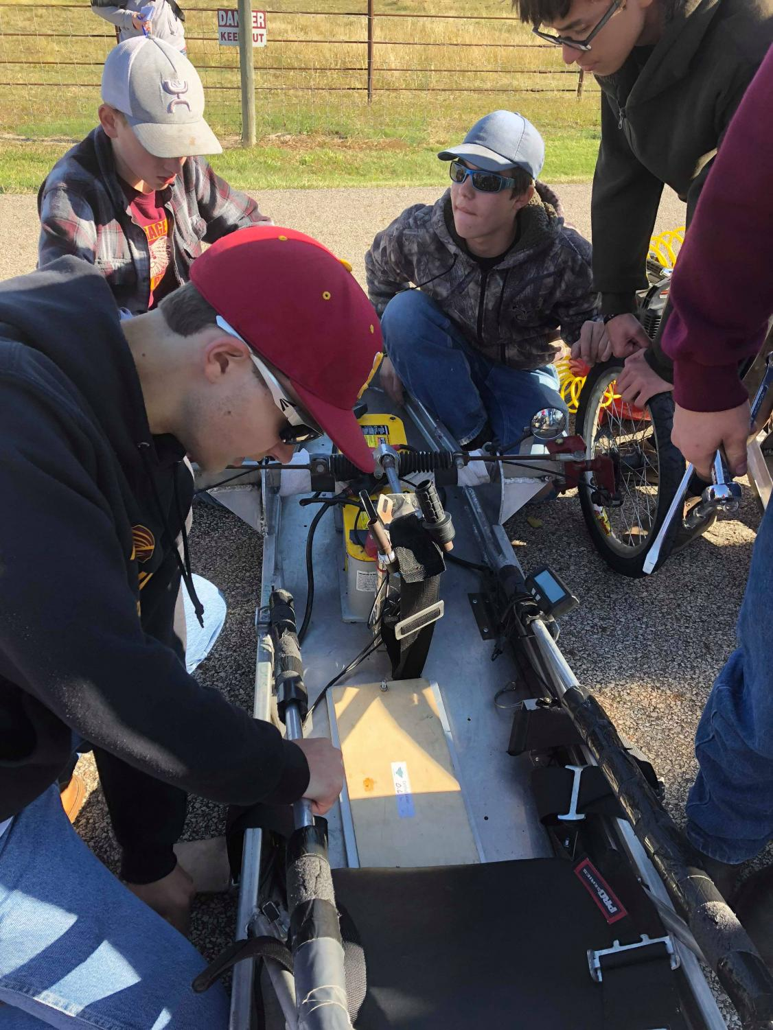 Junior Levi Hickert works on one of the cars at the Electro Rally. The rally was held September 27 at the Hays Municipal Park.