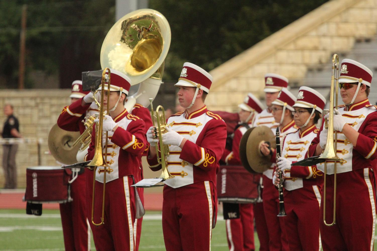 The marching band performs at a home football game. Overall, they received a II rating at contest.