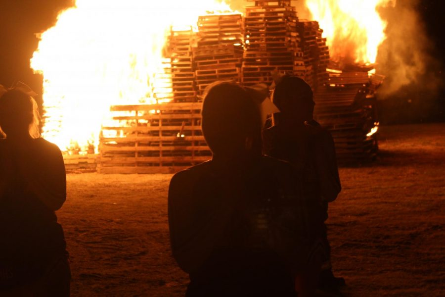 Cheer+leaders+perform+in+front+of+the+bonfire.