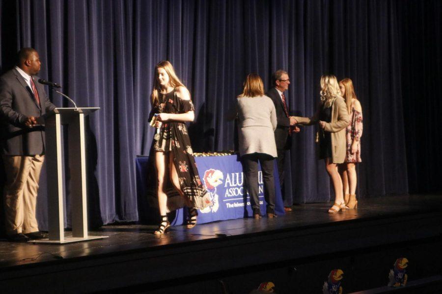 Senior Alyssa Underwood shakes University of Kansas Chancellor Douglas Girod as she receives her medallion.