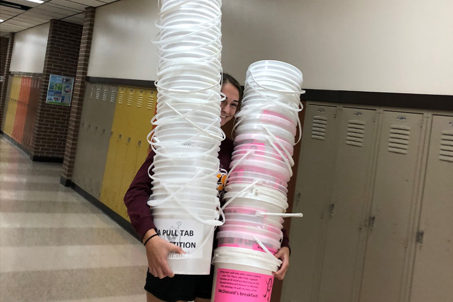 Seniors Kallie Leiker carries donation buckets to prepare for a pull tab competition. Their project, the Ronald McDonald house charity, accepts pull tabs to allow families to spend nights.