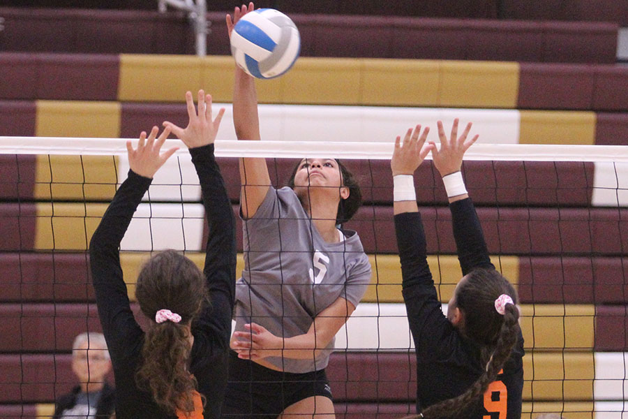 Junior Tasiah Nunnery putting down a kill at a home match against Larned.
