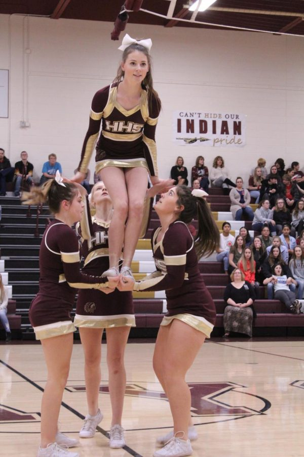 The+cheerleaders+perform+one+of+their+stunts+in+which+sophomore+Stanna+Summers+is+lifted+into+the+air.