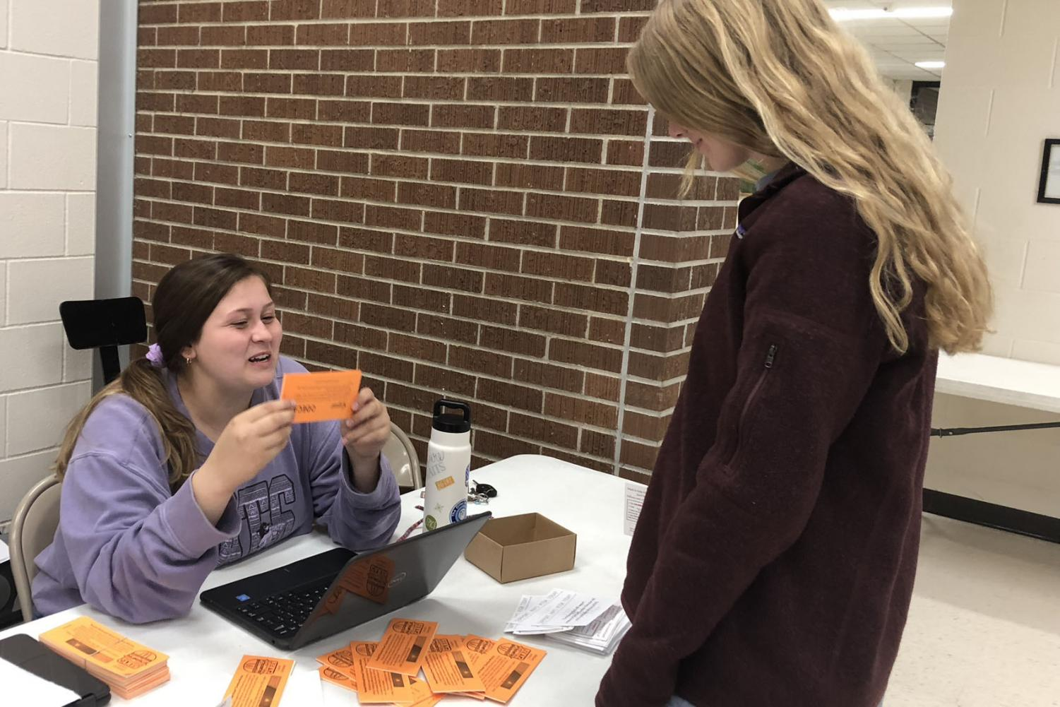 Senior Shyann Schumacher works to sell coupon books at the parent-teacher conferences on Nov. 29. The coupon books raise money for the Ronald McDonald House Charities which allow families with severely ill children to stay for low to no cost.