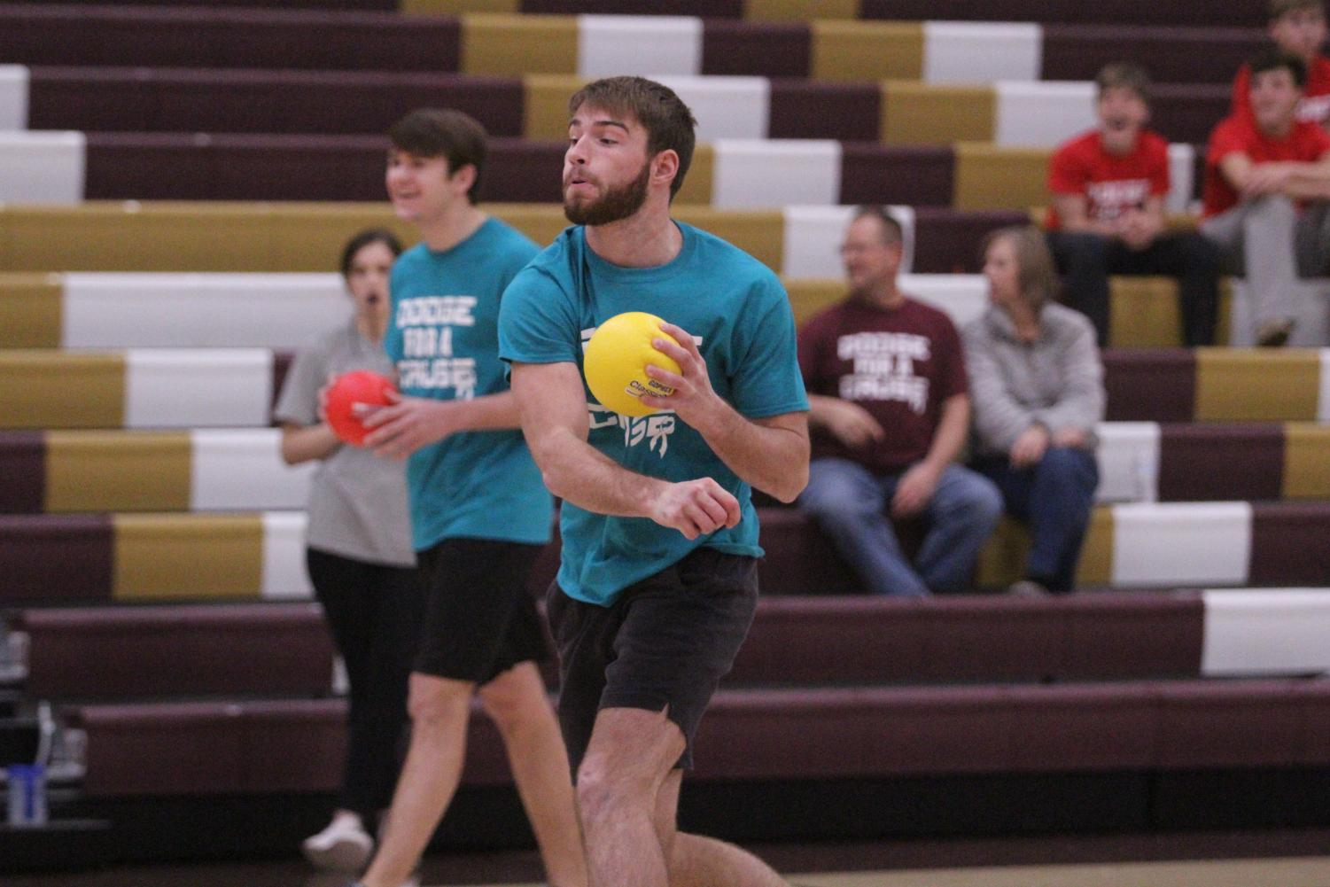 Senior Keaton Markley throws a dodgeball at the opposing.