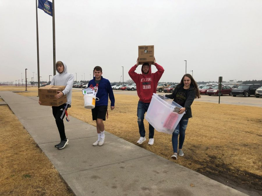 Senior DECA members Connor Teget, Peyton Thorell, and Kallie Leiker carry things for the community service project inside. Leiker carries buckets that will be used for the collection at Dillons on Dec. 8.