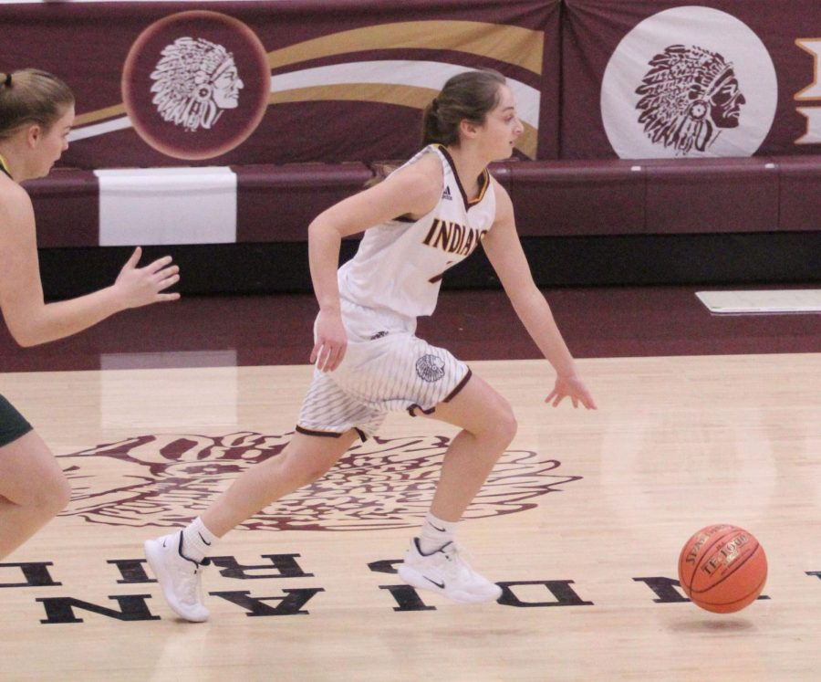 Senior Kallie Leiker dribbles the ball across the court at a previous game against Pratt. The team will play its rival, the Great Bend Panthers on Jan. 8.