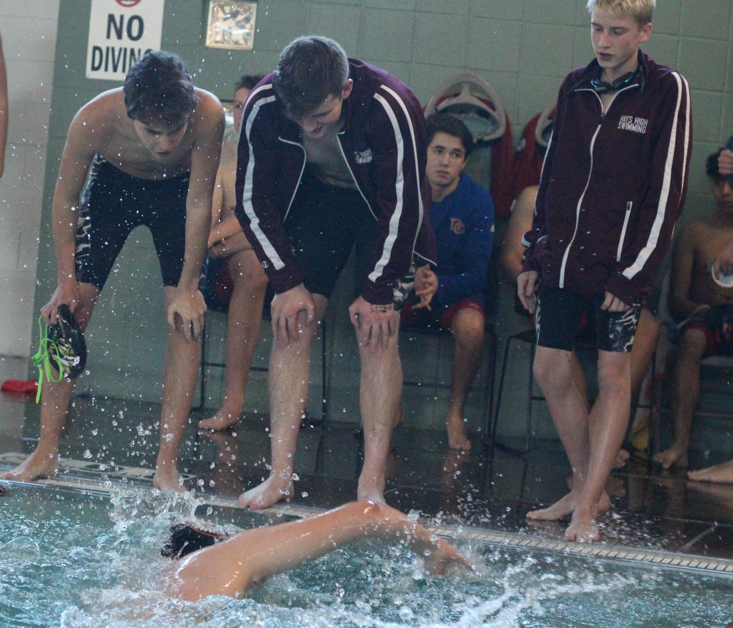 Swim team cheers on junior Carson Ackerman as he finishes the last leg of his race.