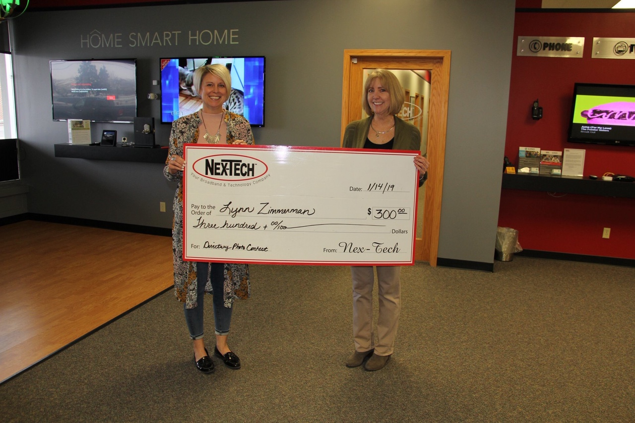Instructor Lynn Zimmerman accepts her check from Nex-Tech. She recently won a Nex-Tech contest and her photo was put on the front cover of the directory.