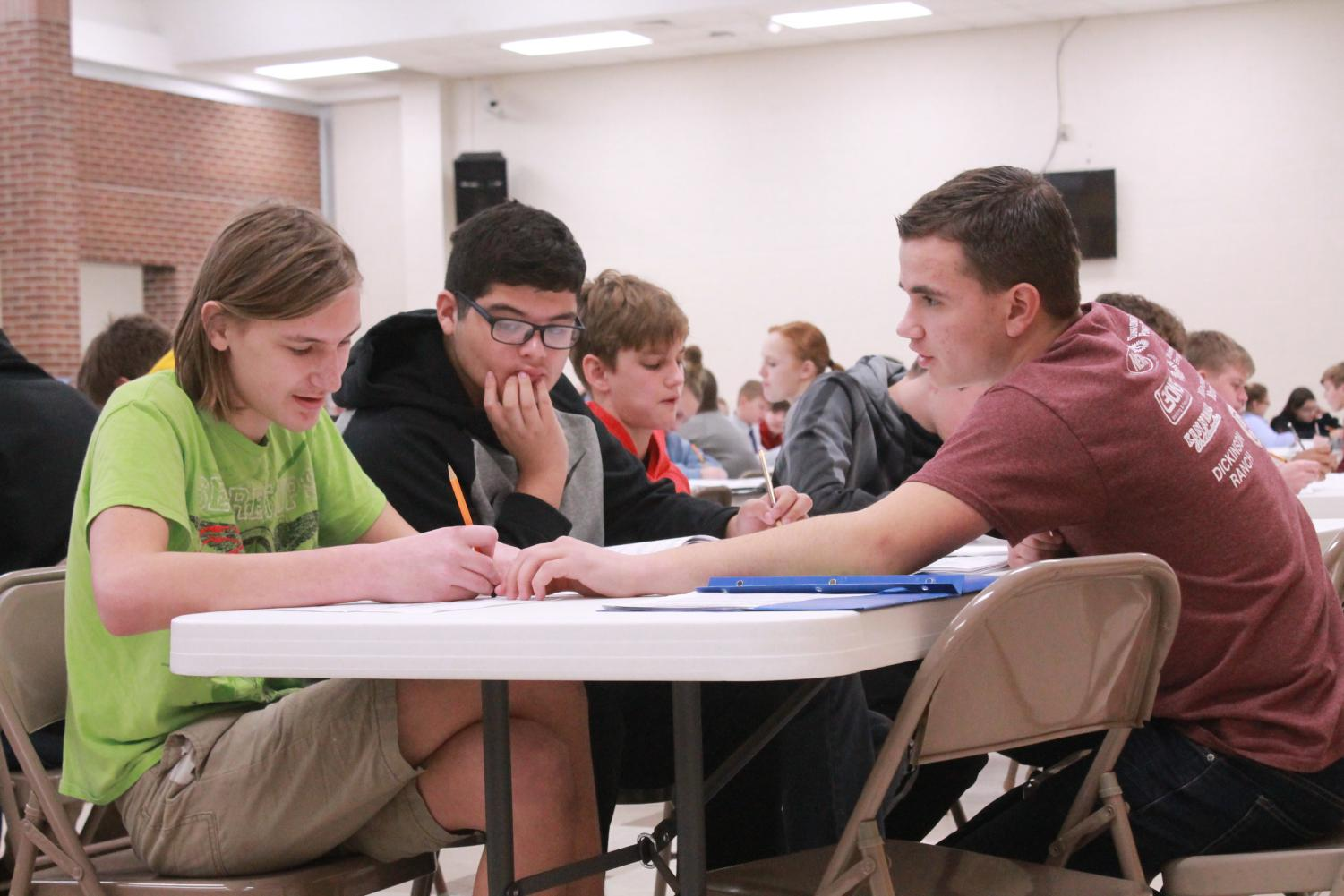 Leadership team member Josh Norris helps students enroll in classes. On Feb. 26, 8th grade parents had a meeting in the lecture hall.