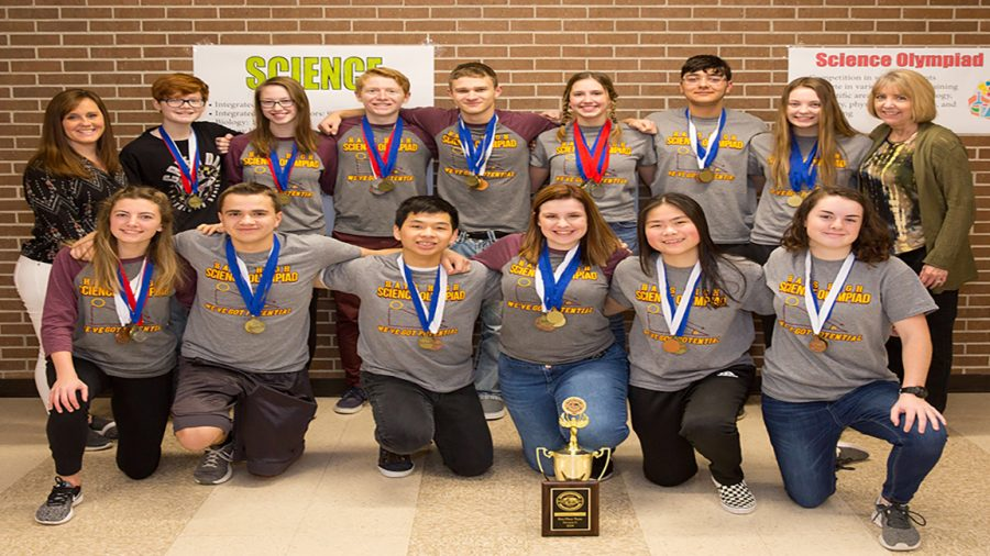 The Science Olympiad team poses with their trophy.