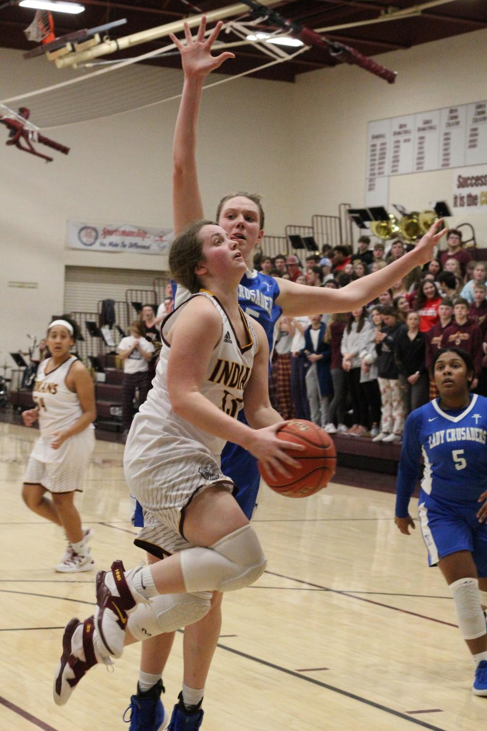 Junior Brooke Denning attempts a basket against Kapaun Mt. Carmel at the first round of Sub-State on Feb. 27. The team is now 14-7 and will play the Goddard Lions on Mar. 1.
