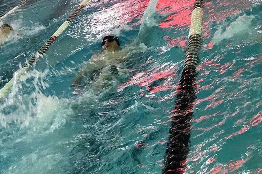 Junior Marshall Perryman swimming backstroke.