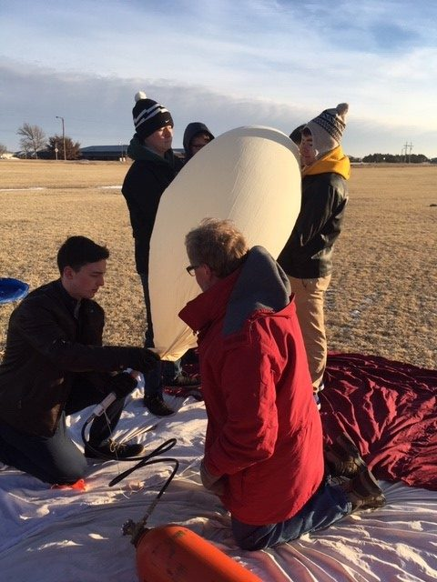 Seniors Garret Rymer, Spencer Wittkorn, Benton McGrath and Cameron Karlin help fill the balloon with helium.
