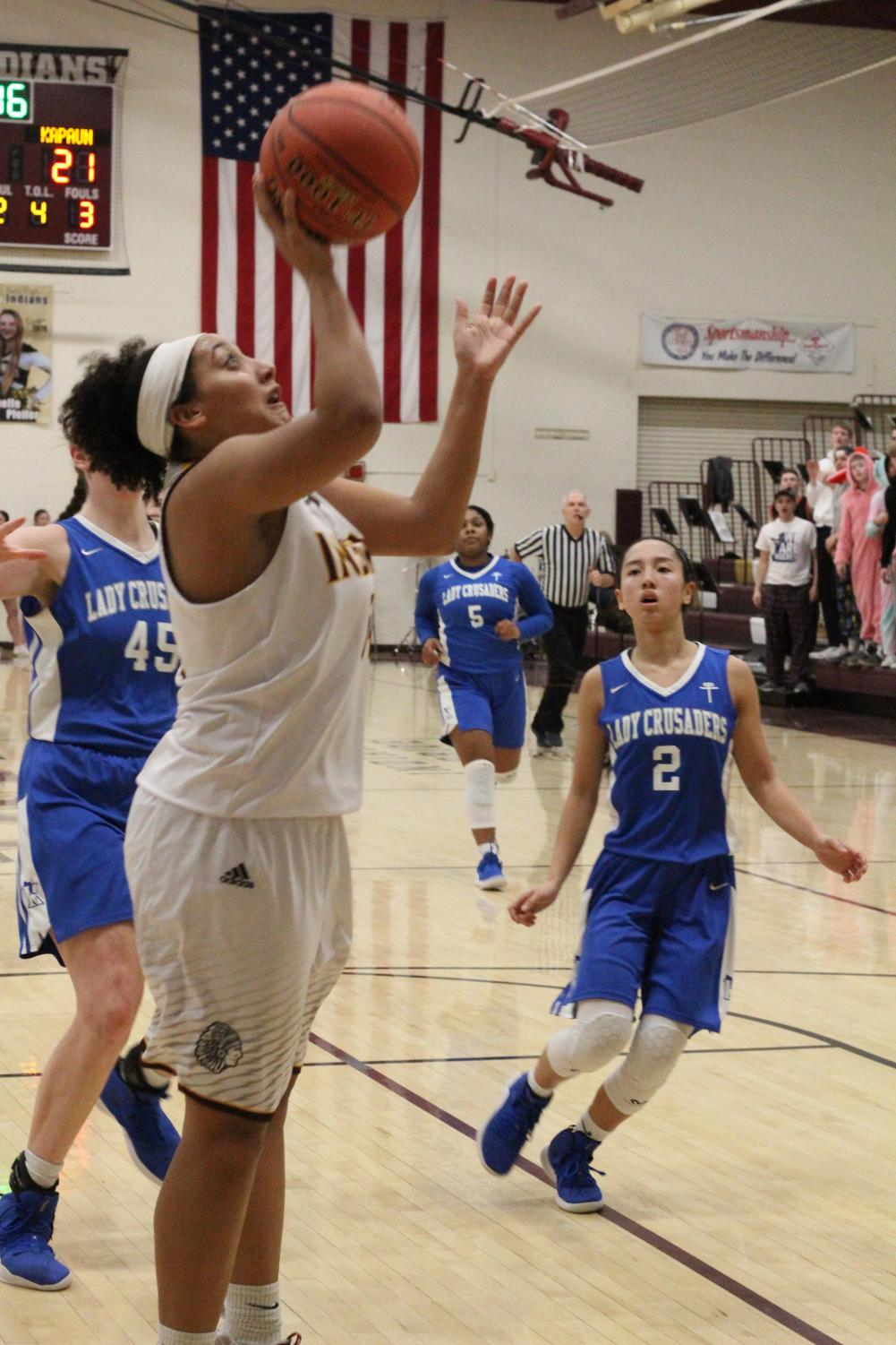 Freshman Taleia McCrae attempts a basket at the first round of Sub-State at home against Kapaun Mt. Carmel. The Indian basketball team ended its season 14-8 after a loss against the Goddard Lions.