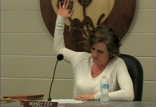 BOE president Mandy Fox raises her hand to vote against the iPads.