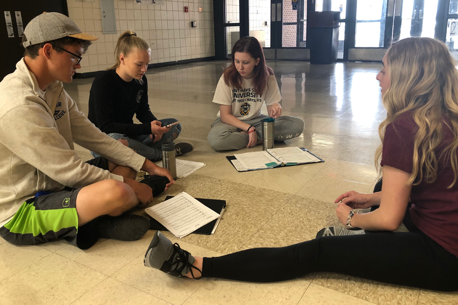 Seniors Zac Wyse, Rebecca Anderson, and sophomore Eliana Buller meet with acapella specialist Shelby Matlock to discuss scheduling and choreography. The Chamber Singers will compete against each other during the Pops Showcase concert on May 4th at 12th Street Auditorium.
