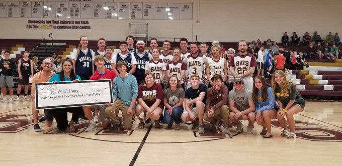 The two basketball teams and StuCo groups stand with the check for the Arc of Central Plains. The two groups were able  to present them with a 4000 dollar check to help fund the ARC Park.