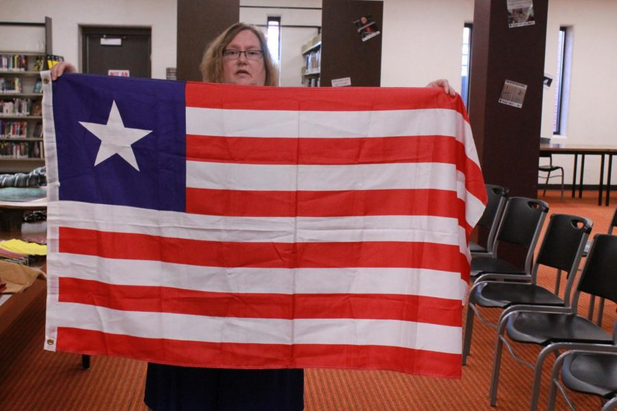 Folkerts+holds+up+the+Liberian+flag.+The+flag+was+based+off+of+the+United+States%2C+taking+the+stripes+and+blue+background+and+using+one+star+to+represent+the+one+country.+