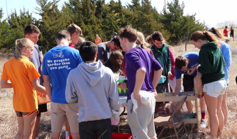 Student circle around the prize table in the outdoor classroom. Students took the slips of paper found in each of the eggs to the table to claim their prizes.