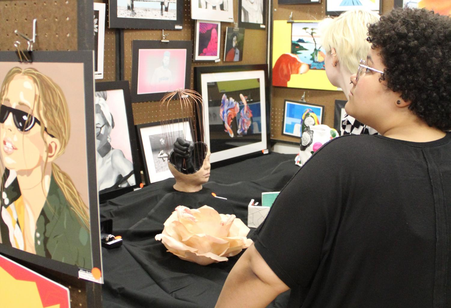 Seniors Mollie Hoar and Taysia McCoy view the work displayed in a booth from one of the attending schools. Many art students contributed to the Hays High School art booth.