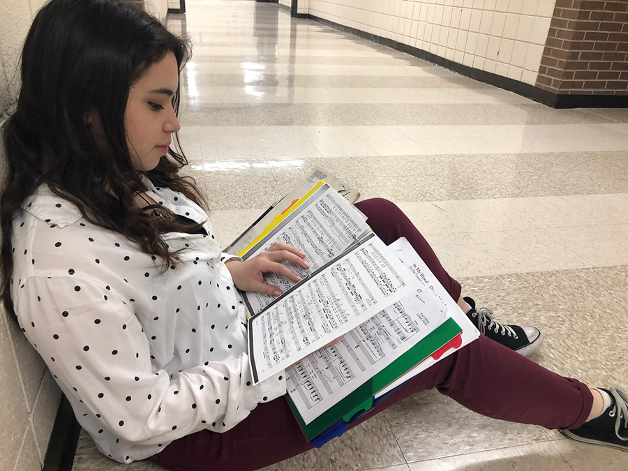 Sophomore Alisara Arial takes a few minutes to study her solo score in the hallway during seminar. The KSHSAA Regional Solo and Small Ensemble Festival will take place on March 6 at Barton Community College.