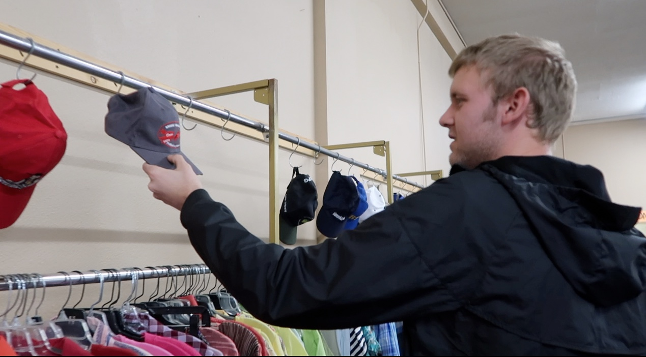 Senior Calvin Duden looks at hats at the local thrift store The Arc.