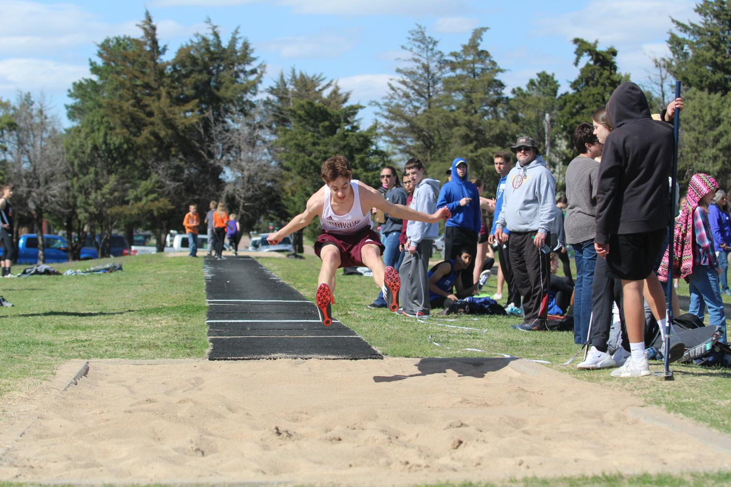 Sophomore Kyler Beckman jumps at a previous track meet in Larned. Both track teams competed at the McPherson Varsity Invitational on April 25.