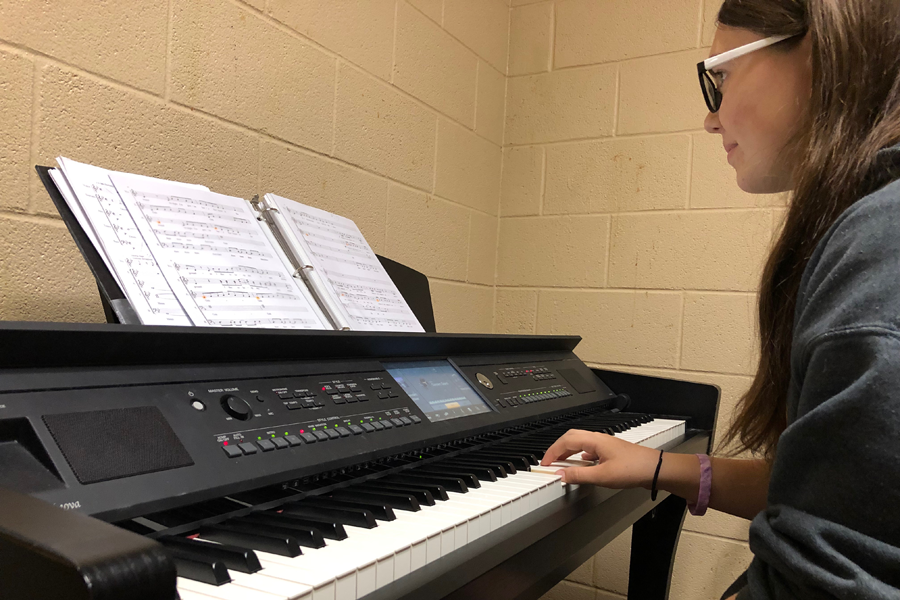 Sophomore Alexis White reviews a part of one of her group's acapella songs in a practice room during seminar.