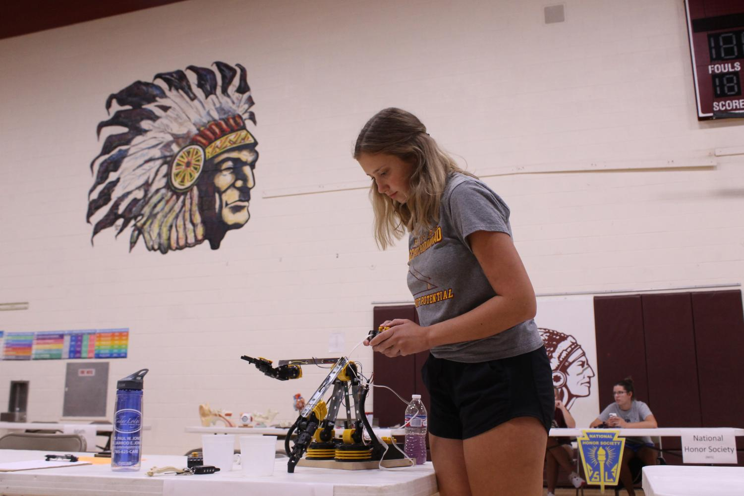 Junior Marrissa Raynesford operates the robitic arm for the Science Olympiad Team during PRIDE Night.