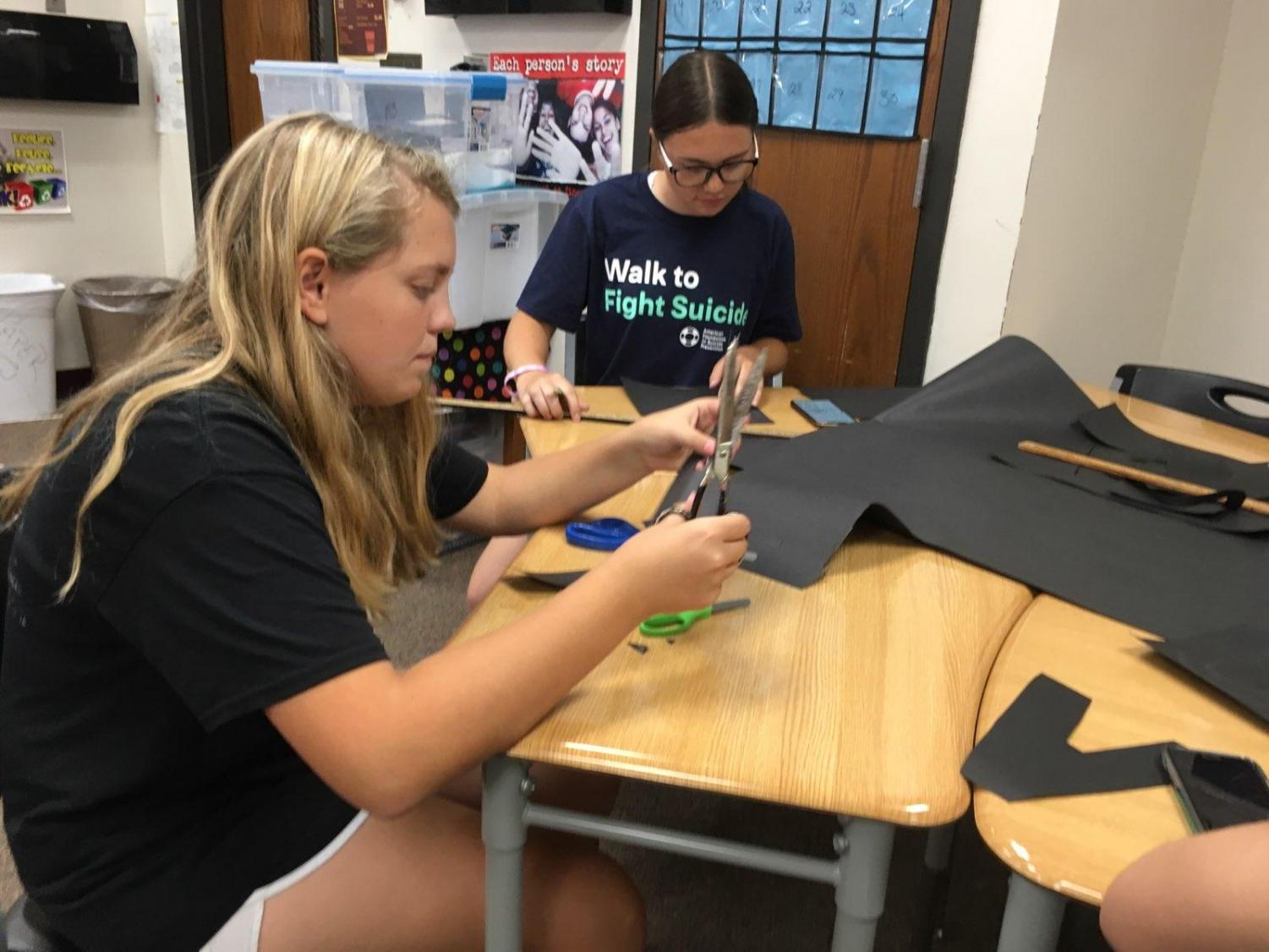 Junior Alexis White and sophomore Summer Schneider work on decorations for this year's Homecoming.