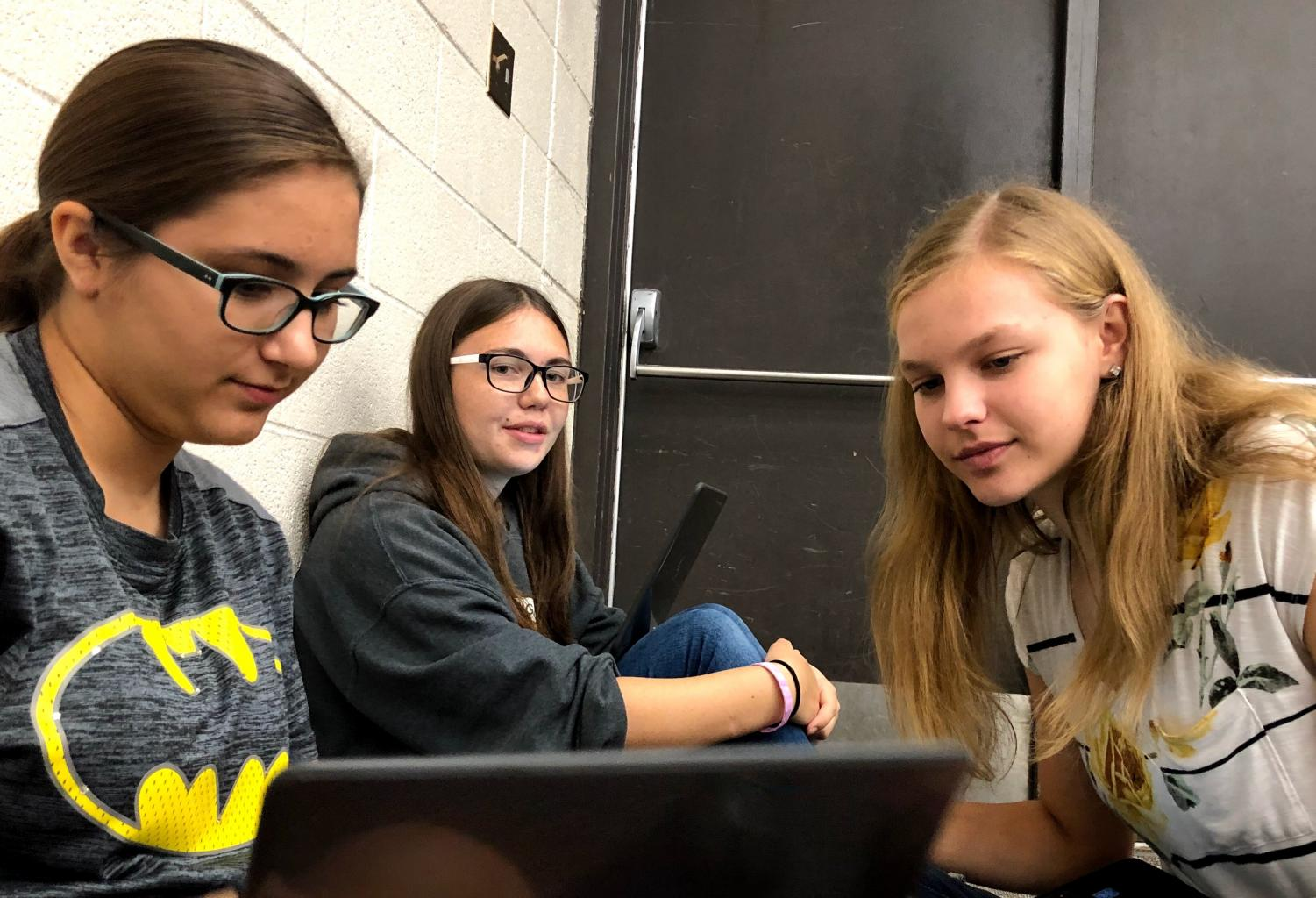 Senior Sierra Adkins, junior Alexis White and sophomore Samantha Vesper watch a promotional video for a disaster relief charity during the research time in Chamber Singers. This year's featured organization is All Hands and Hearts.